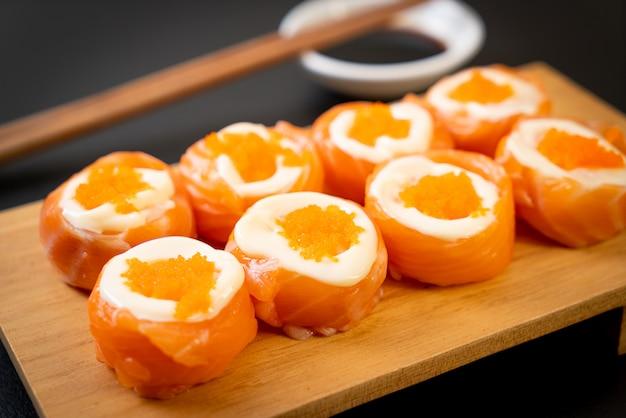 Rollo de sushi de salmón fresco con mayonesa y huevo de camarones