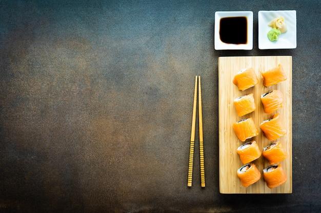 Rollo de sushi de salmón pescado carne maki en placa de madera