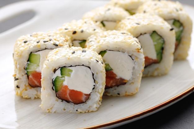 Rollo de sushi con salmón, queso philadelphia y sésamo en placa de cerca