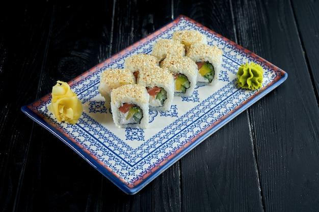 Rollo de sushi en semillas de sésamo con salmón, aguacate y queso crema en un plato azul.