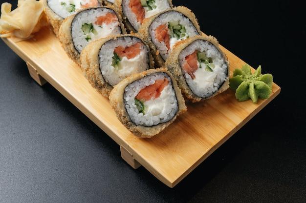 Rollo de tempura con salmón y aguacate sobre tabla de madera