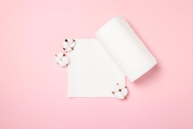 Rollo de toallas de papel y flores de algodón sobre una superficie rosa. el concepto es 100 producto natural, delicado y suave. vista plana, vista superior