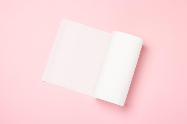 Rollo de toallas de papel sobre una superficie rosa. el concepto es 100 producto natural, delicado y suave. vista plana, vista superior.