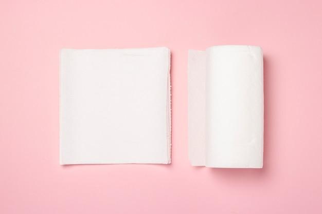 Rollo de toallas de papel y toallas de pocas piezas sobre una superficie rosa. el concepto es 100 producto natural, delicado y suave. vista plana, vista superior.