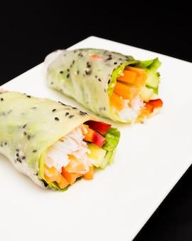Rollo de verano lleno de verduras de colores en un plato blanco