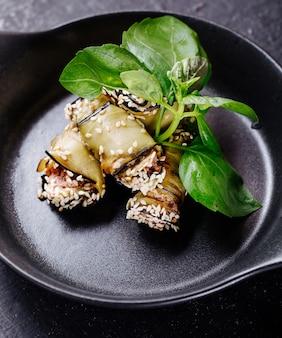 Rollos de berenjenas con hojas basílicas dentro de una sartén negra.