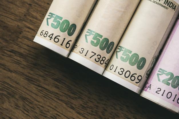 Rollos del billete de banco del dinero de la rupia india en el fondo de madera