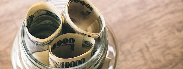 Rollos de billetes de dinero yen japonés en el tarro de cristal