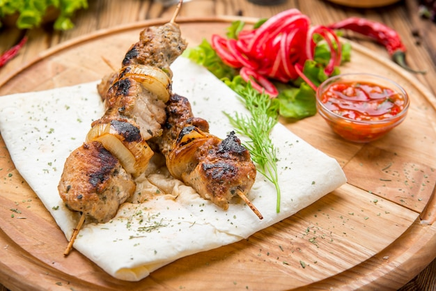 Rollos de carne a la parrilla con cebolla roja y zumaque en pita