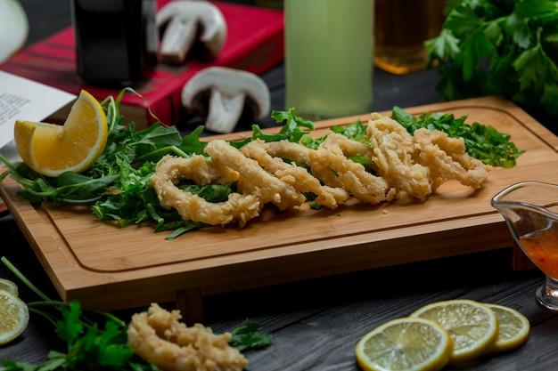 Rollos de cebolla asada con hierbas frescas y rodajas de limón.