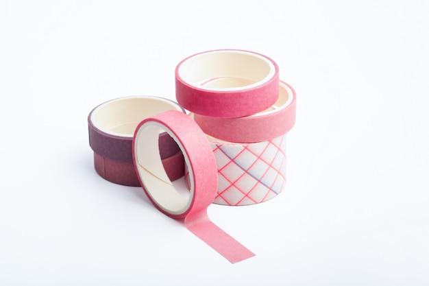 Rollos de cinta washi rosa y morado sobre una mesa blanca