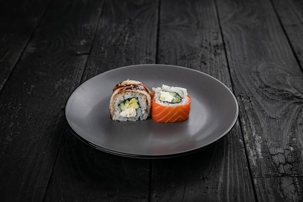Rollos de cocina japonesa sobre un plato redondo sobre una mesa negra