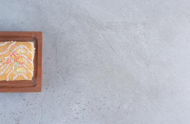 Rollos dulces sabrosos con sabor a vainilla sobre tabla de madera.
