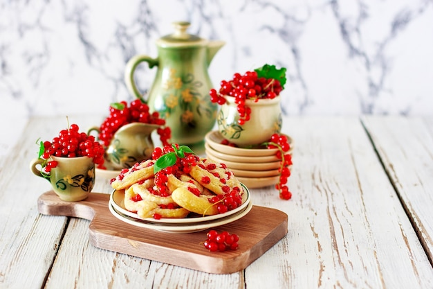 Rollos de galleta de requesón con grosellas rojas en plato de cerámica con té o café de cerámica vintage, hora del té, desayuno, dulces de verano