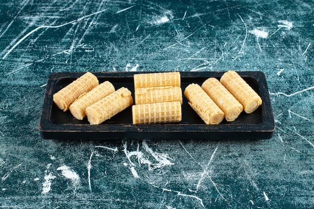 Rollos de gofres deliciosos en placa negra.