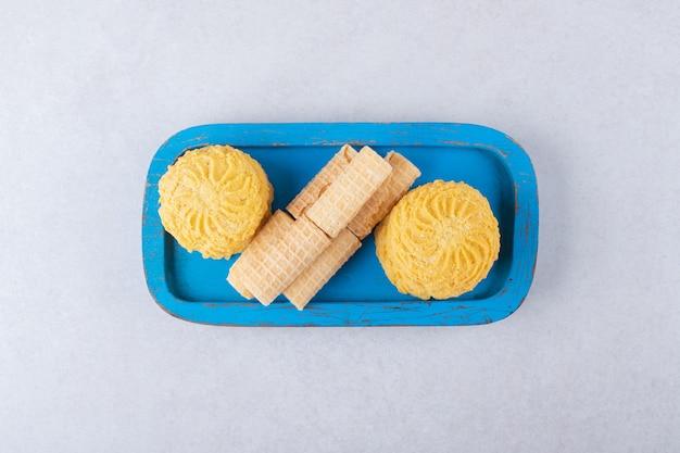 Rollos de gofres y galletas en la placa de madera, el mármol.