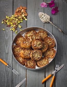 Rollos hechos con semillas de calabaza y almendras en una olla de metal sobre una superficie de madera