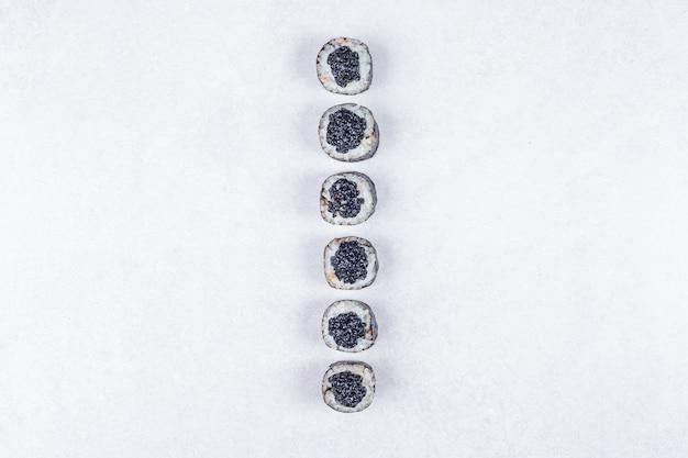 Rollos de maki decorados con caviar negro sobre fondo blanco.