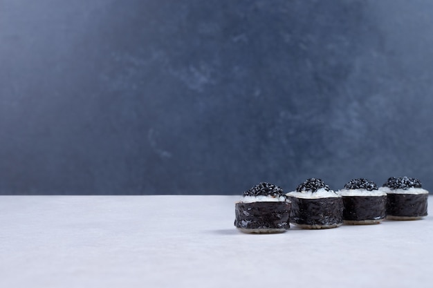 Rollos de maki decorados con caviar negro sobre mesa blanca.