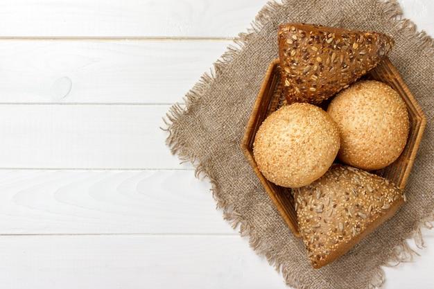 Rollos de pan en la cesta sobre fondo de madera rústico