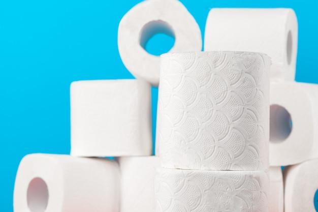 Rollos de papel higiénico apilados contra azul