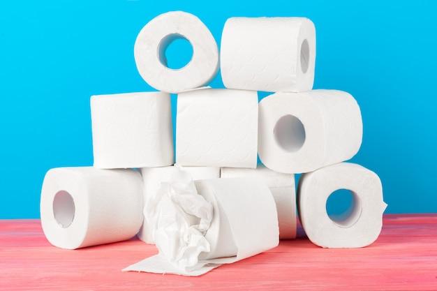 Rollos de papel higiénico apilados sobre fondo azul.