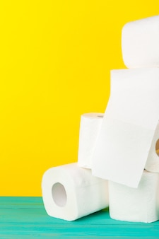 Rollos de papel higiénico apilados sobre papel amarillo