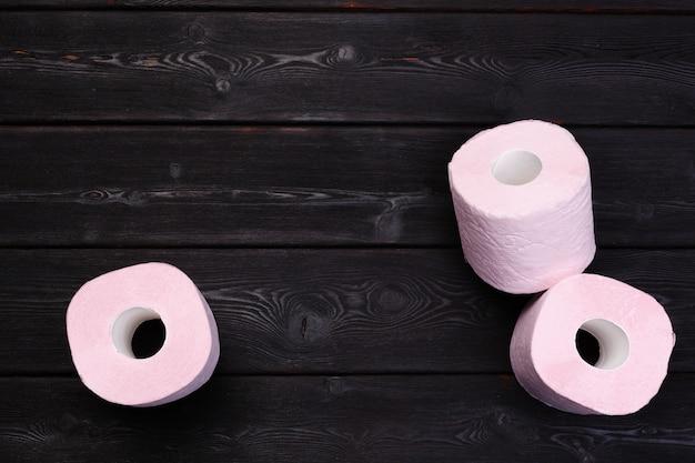 Rollos de papel higiénico rosa pastel en madera negra