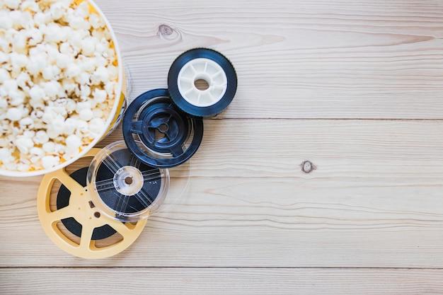 Rollos de película y cubo sobre palomitas de maíz