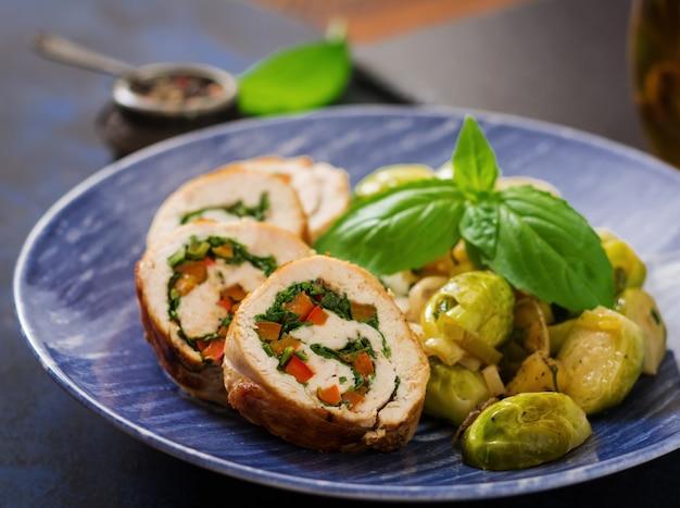 Rollos de pollo con verduras, adornado con coles de bruselas guisadas, manzanas y puerros en un plato azul.