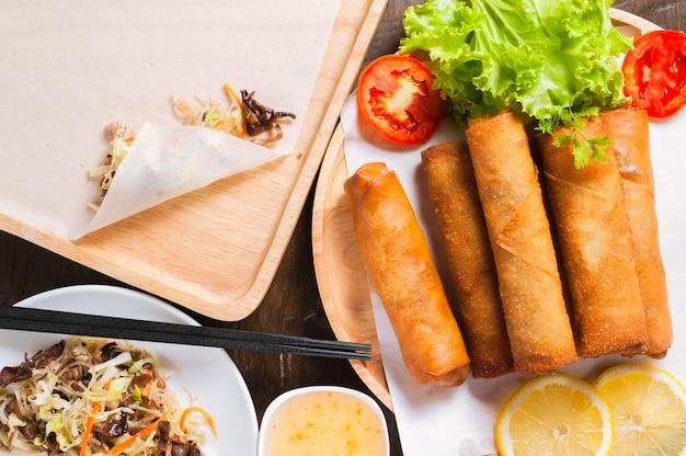 Rollos de primavera fritos crujientes con salsa de ciruela y ensalada, rodajas de limón en la mesa de madera