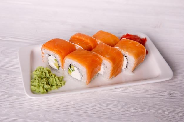 Rollos de salmón, queso crema y aguacate, menú del restaurante sobre un fondo de madera clara