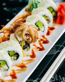 Rollos de sushi con aguacate de pulpo bebé cubierto con sésamo