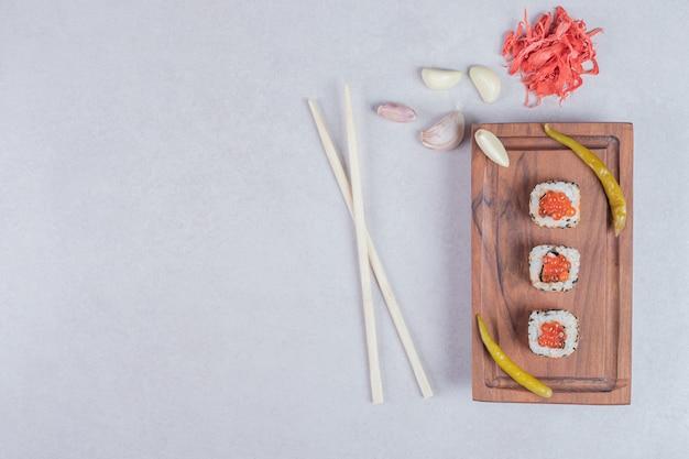Rollos de sushi de alaska decorados con caviar rojo sobre fondo blanco con palillos y jengibre encurtido.