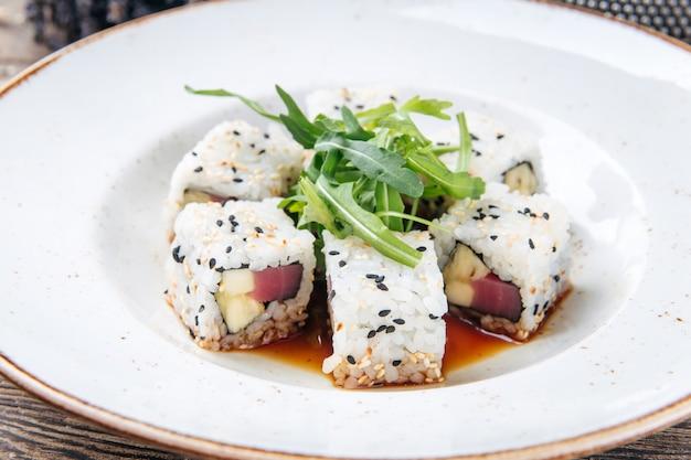 Rollos de sushi de atún arroz semillas de sésamo y salsa de soja