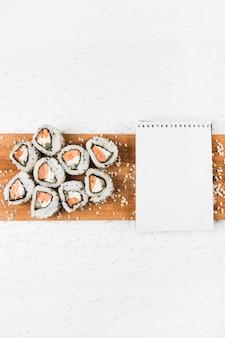 Rollos de sushi y bloc de notas en espiral en bandeja de madera con salpicaduras de arroz crudo sobre fondo blanco