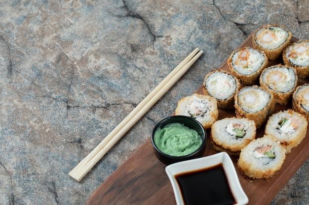 Rollos de sushi caliente frito con queso crema, wasabi y salsa de soja sobre una tabla de madera.