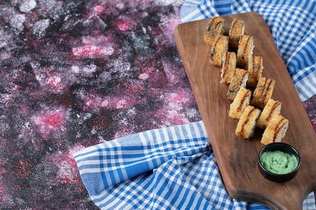 Rollos de sushi caliente frito sobre una tabla de madera con salsa de wasabi.