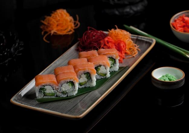 Rollos de sushi caliente con salmón ahumado envuelto desde afuera