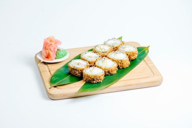 Rollos de sushi caliente servido en hojas sobre tablero de madera en fondo blanco.