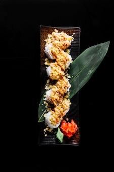 Rollos de sushi caliente sobre una hoja verde con jengibre y wasabi.