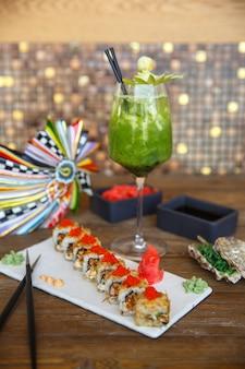 Rollos de sushi calientes cubiertos con tobiko rojo, servidos con jengibre y wasabi