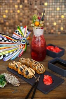 Rollos de sushi calientes servidos con jengibre y wasabi en tablero de piedra negra