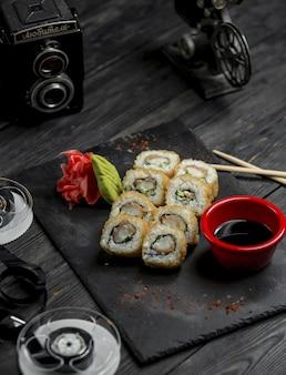 Rollos de sushi, california caliente con salsa y jengibre rojo en bandeja de piedra
