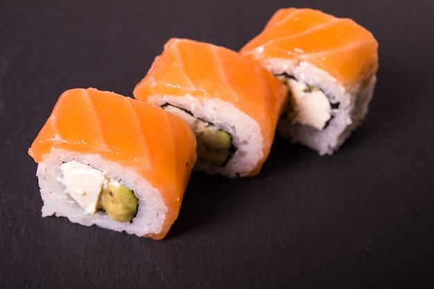 Los rollos de sushi de california de filadelfia se encuentran en una placa de cerámica negra