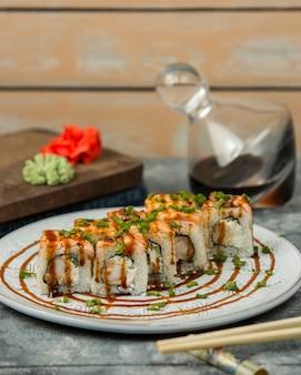 Rollos de sushi con camarones y pepino cubiertos con salmón, salsa de soja y cebolla