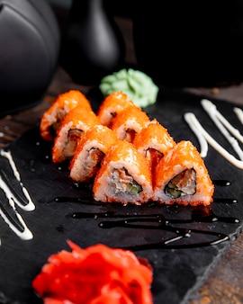Rollos de sushi con caviar tãbiko servidos con jengibre y wasabi