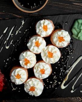 Rollos de sushi con crema y caviar rojo servidos con jengibre y wasabi