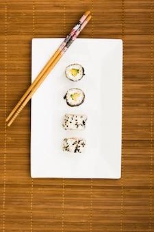 Rollos de sushi dispuestos en una fila en lugar blanco con palillos de madera sobre mantel