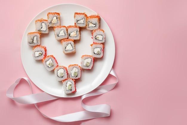 Rollos de sushi dispuestos en forma de corazón en un plato